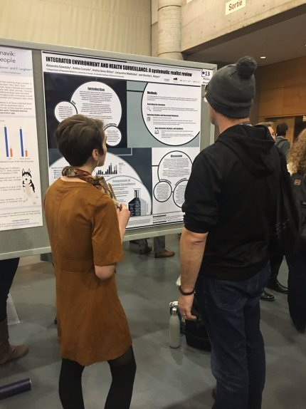 Alexandra Sawatzky (left) discussing her poster on integrated- environmental surveillance in the Circumpolar North; photo credit - Sherilee Harper