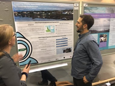Mark Andrachuk (right) discussing his poster on the eNuk monitoring app in Rigolet, NL; photo credit - Dan Gillis.